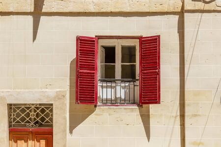 Window with wooden opened red shutters on the wall of old building in Valletta,  Malta Stockfoto