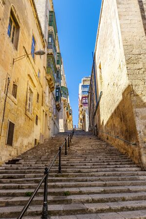 Maltese narrow street with long staircase in Valletta, Malta
