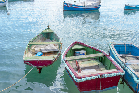 Maltese boats float in the harbor of Marsaxlokk, Malta. the fishing boats are decorated with the eye of Osiris to keep the fishers safe at sea