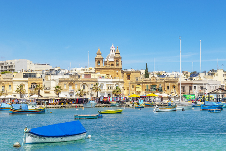 The traditional luzzu boats in the harbor of fishing village Marsaxlokk in Malta