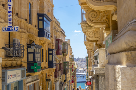 Valletta, Malta - May 1, 2019: Typical narrow maltese streets with colorful traditional windows and wooden shutters and balconies, clear blue sky on a summer day, Valletta, Malta