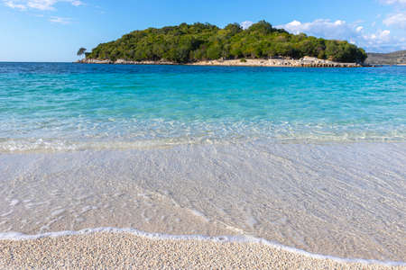 Crystal clear water and sand on beach of Ksamil in Albania, border between the Adriatic and Ionian seas