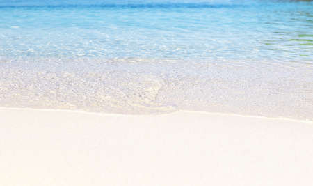 Close up photo of crystal clear water and sand on beach of Ksamil in Albania, border between the Adriatic and Ionian seas