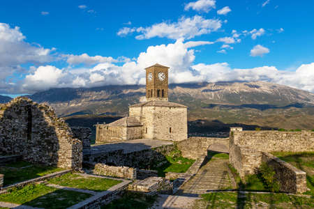 Scenic view of clock tower in castle of Gjirokastra with mountains and clouds on blue sky, Gjirokastra, Albania