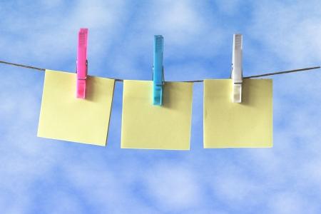clothes washing: Col�quela en notas colgando de una l�nea de lavado contra el cielo azul Foto de archivo