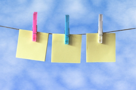 pegs: Post it Notes hanging on a washing line against blue sky Stock Photo