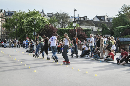 PARIS, FRANCE - MAY 4   FouriIn-line skaters in a line doining slalem tricks for a crowed on 4 May 2008 in Paris France