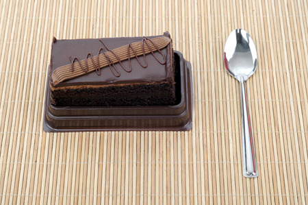 A tasty slice cake with spoon on bamboo mat photo