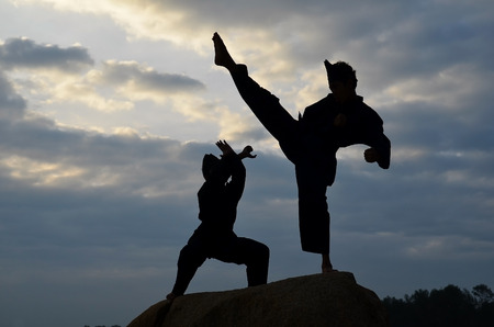 malay: Silhouette of two young boys sparring a pencak silat, Malay traditional discipline martial art
