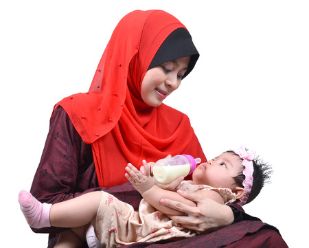 muslim baby girl: Young Asian muslim mother enjoying feeding her cute baby girl with a milk bottle isolated on white background