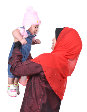 Young Asian muslim mother playing and smiling with her cute baby girl isolated on white background photo