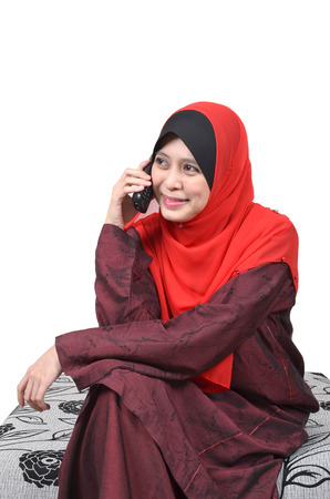 Beautiful young muslim woman happy talking on mobile phone isolated on white background  photo