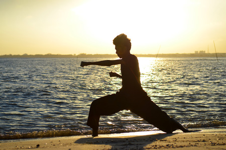 Silhouette of young boy performing a pencak silat, Malay traditional discipline martial art in evening at the beach photo