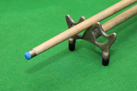 snooker cue: Snooker cue with rest isolated on green background