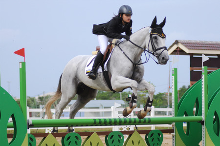 grey horses: Unidentified equestrian female rider show jump horse trying to overcome hurdles at Malaysia sport, Sukma in Pahang, Malaysia