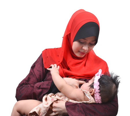 Young Asian muslim mother breastfeeding her cute baby girl isolated on white background photo