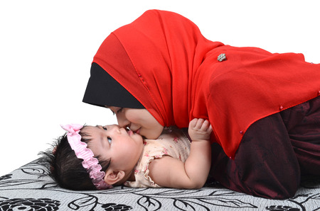 Young Asian muslim mother kissing her cute baby girl isolated on white background photo