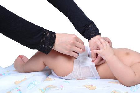 Jeune mère musulmane changer la couche de son bébé isolé sur fond blanc