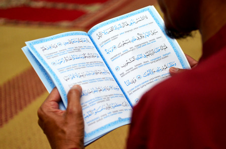 pious: A muslim male was reading holy Quran, focus pointed at the middle and shallow DOF Stock Photo