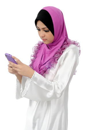 Beautiful young muslim woman messaging on mobile phone isolated on white background photo