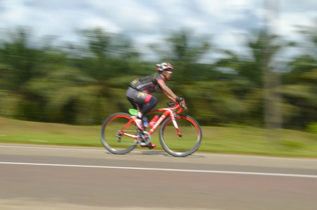 action blur: Motion blur of a cyclist in action during a cycling tour