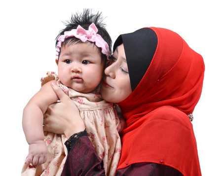 muslim baby girl: Young Asian muslim mother kissing her cute baby girl isolated on white background