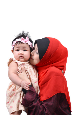 muslim baby: Young Asian muslim mother kissing her cute baby girl isolated on white background