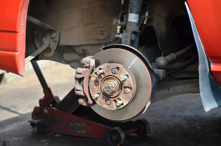 jacked: Front disk brake with caliper and detail of the wheel hub