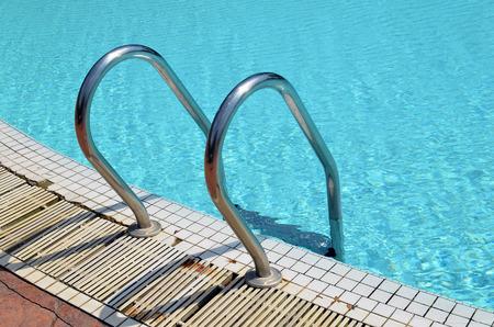 pool bars: Grab bars ladder in the blue swimming pool Stock Photo