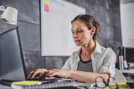 Woman wearing white shirt using laptop at office