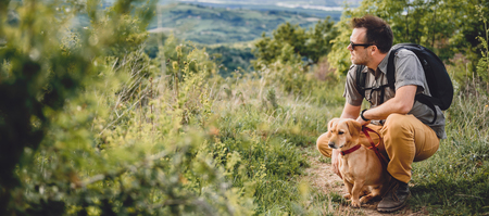 conquering adversity: Man wearing sunglasses with a small yellow dog resting at the hiking trail Stock Photo