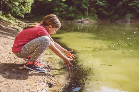 Girl squatting by the lake and catching tadpole