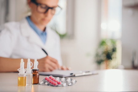 Medical supplies on table and doctor in the background writing prescription