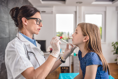 면봉을 사용하여 환자의 목구멍에서 샘플을 채취 한 여성 소아과 의사 스톡 콘텐츠