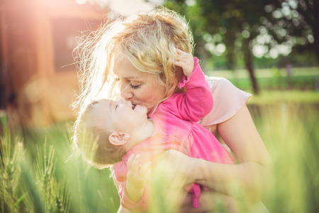embraced: Young mother holding and kissing her baby in the grass