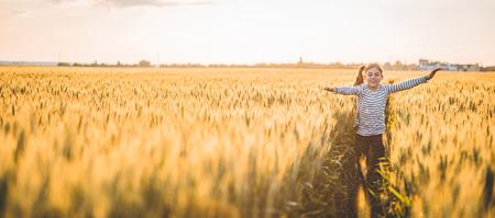 小さな少女が日没時十字の麦畑