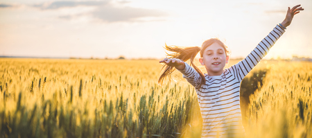 Little girl running cross the wheat field at sunset