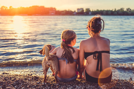 Mother, daughter and small yellow dog enjoying on the beach 免版税图像 - 83428152