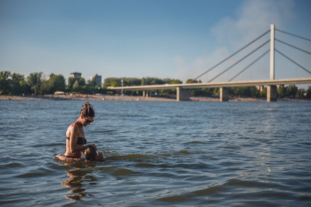 Mother learning daughter to swim in the river by the bridge