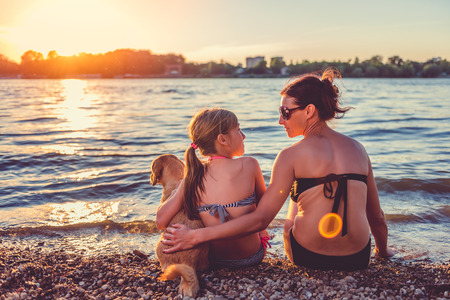 Mother, daughter and small yellow dog enjoying on the beach 免版税图像 - 83390736