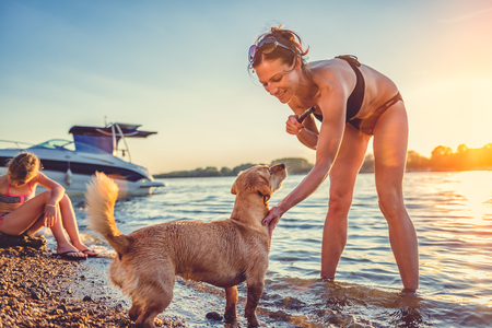 Mother, daughter and small yellow dog enjoying on the beach 免版税图像 - 83390770