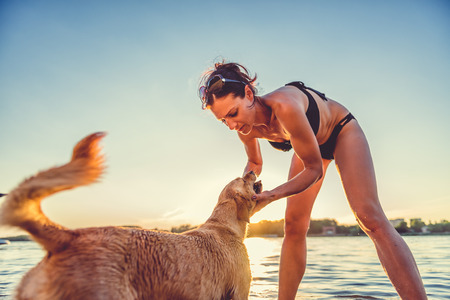 Woman and her dog playing on the beach