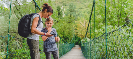 Mother and daughter standing on wooden suspension bridge in the forest and using smart phone to navigate