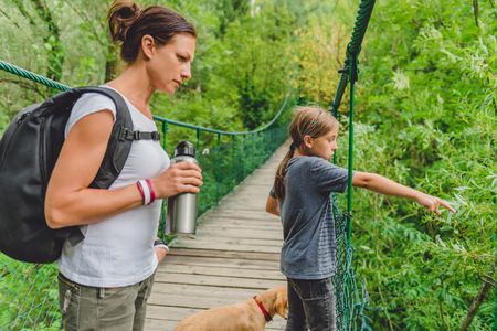 Mother and daughter standing on wooden suspension bridge with small yellow dog and looking at the river below