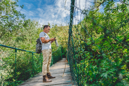 Hiker standing on the wooden suspension bridge in the forest and using smart phone to navigate