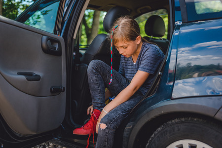 Little girl sitting in the car and putting on red sneakers