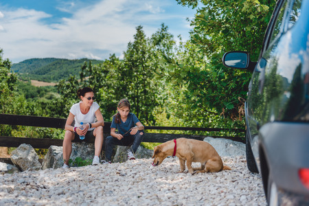 Mother and daughter on a road trip with dog taking a break and sitting on a rock 免版税图像