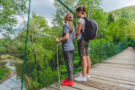 Mother and daughter standing on wooden suspension bridge and looking at the small river below