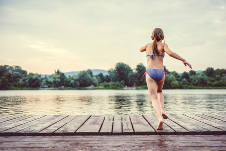 Girl jumping into water from dock 免版税图像 - 85011164