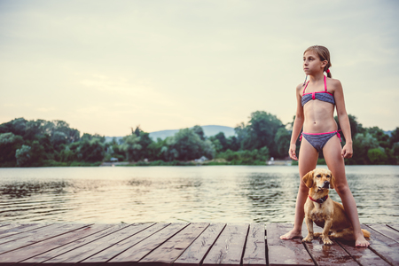 Little girl and her dog standing on a dock by the river